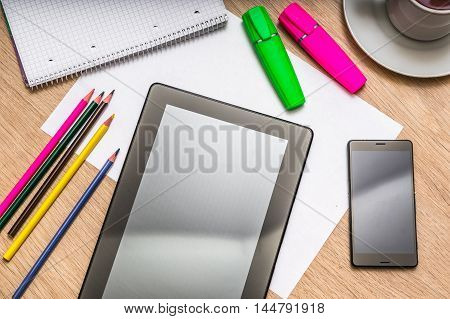 Tablet, Mobile Phone, Paper, Pencils And Cup Of Coffee On Table