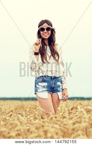 nature, summer, youth culture and people concept - smiling young hippie woman in sunglasses chewing straw on cereal field