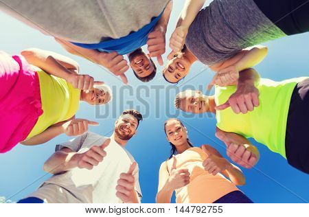 fitness, sport, friendship and healthy lifestyle concept - group of happy teenage friends in circle outdoors showing thumbs up