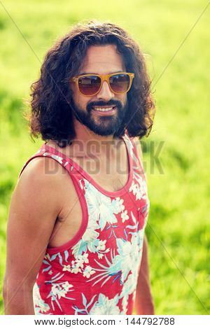 nature, summer, youth culture and people concept - smiling young hippie man in sunglasses on green field