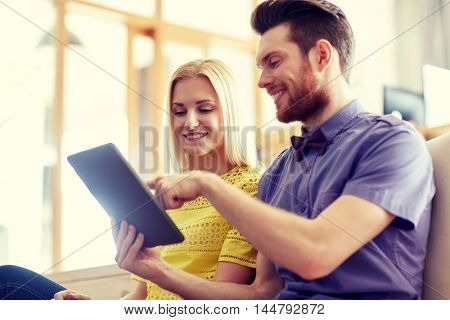 business, technology, startup and people concept - happy creative team with tablet pc computer in office