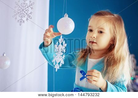 little girl playing with balls and snowflakes. The concept of New Year and Christmas