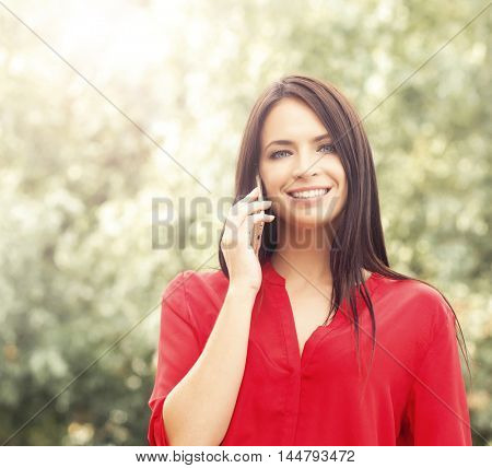 Young beautiful woman in red blouse outside in the park with a new smartphone.