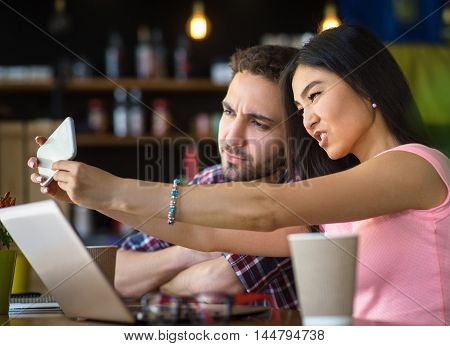 Romance, Valentine concepts. Happy romantic couple making selfies on mobile or smart phone while having date in restaurant or cafe.
