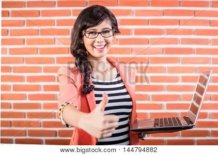 Indonesian college student with Laptop showing thumb