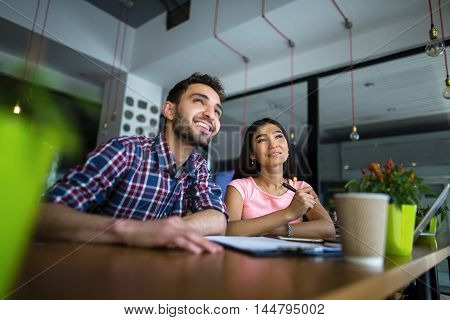 Portrait of business or freelance man and woman working in restaurant or cafe. Happy people looking upwards. Business or freelance concept.