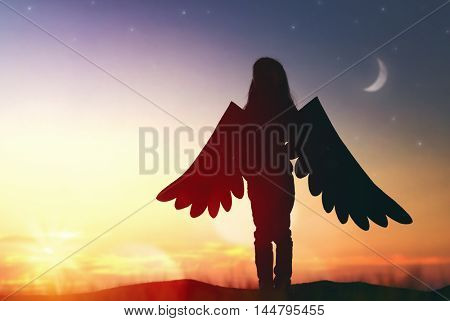 Little girl plays outdoors. Child on the background of sunset sky. Kid with the wings of a bird dreams of flying.