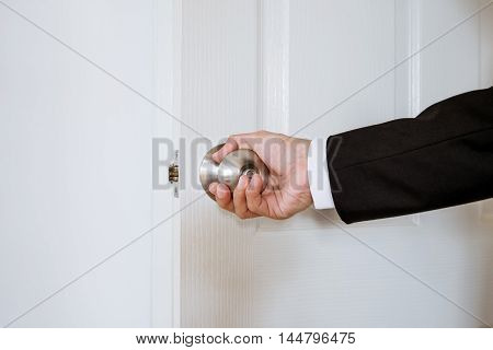 Businessman hand holding door knob, opening or closing door, with bright behind the door