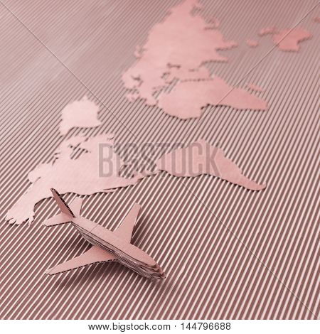 Airplane and world map made of cardboard. Square format, selective DOF. Red colorized.