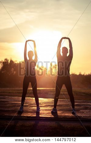 Two silhouettes of young adults doing warming up exercises at sunset. Fitness or running workout outdoors.