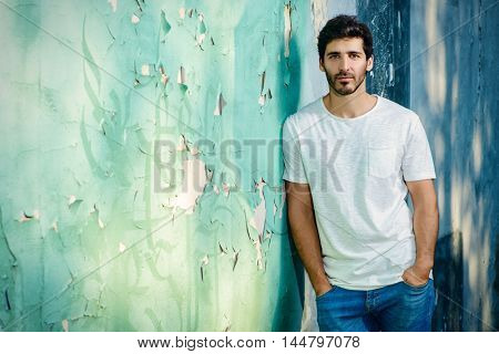 Portrait of a handsome young man in jeans and white t-shirt leaning to the old wall.