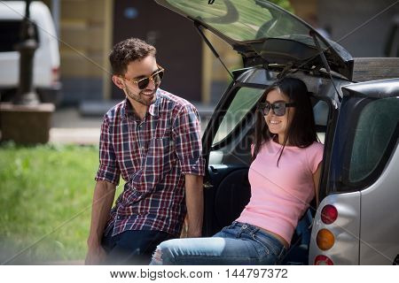 Happy tourist man and woman sitting in car and smiling to each other. People posing outdoors and ready to travel abroad.