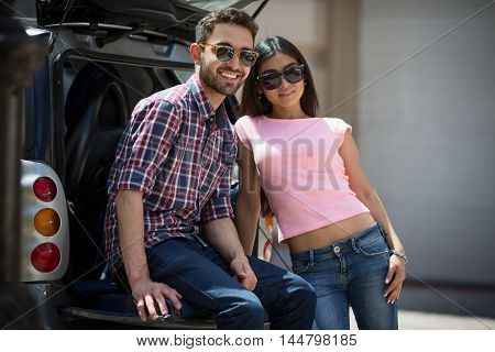 Happy model man and woman posing near car. Models posing for photographer. Fashion or vogue concept. Fashion or vogue magazine.