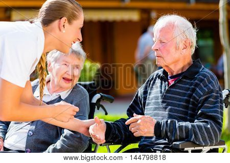 Seniors, couple of man and woman sitting in wheelchair, nurse holding hands with them