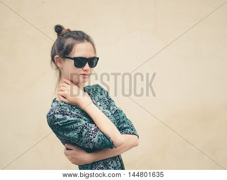 Fashionable serious young woman in black sunglasses posing near wall with copy space