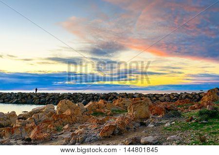 Fisherman silhouette at sunset with clouds above the sea South Australian shore
