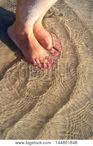 Woman's bare feet closeup with fresh pedicure in the water at the beach.