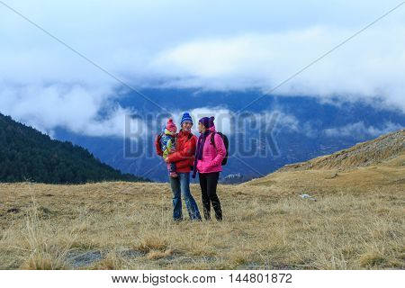 happy loving family with little child hiking in winter mountains