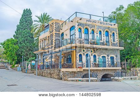 The old restored stone building located on the bank of Sea of Galilee is used as the restaurant with cozy outdoor terrace Tiberias Israel.