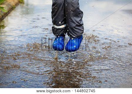 child playing in muddy puddle, kids seasonal activities