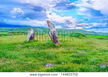 Two ancient stones in Zorats Karer tilted to each other with the cloudy highlands on the background Syunik Province Armenia.