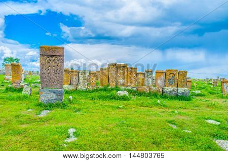 The row of medieval khachkars tilted to each other among the lush greenery of old cemetery Noratus Armenia.