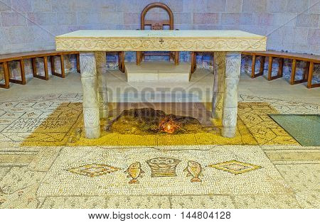 TABGHA ISRAEL - FEBRUARY 22 2016: The stone Altar of the Multiplication Church with the block of limestone on which miraculous fish and loaves were laid according to christian believes on February 22 in Tabgha.