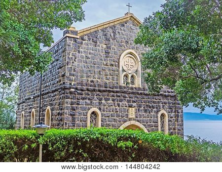 The Church of the Primacy of St Peter located in shady garden on the bank of Kinneret Lake also known as the Sea of Galilee Tabgha Israel.