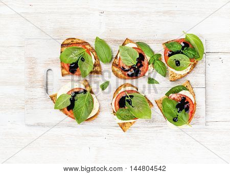 Caprese sandwiches with tomato, mozzarella cheese, basil and balsamic glaze on white painted wooden background, top view, horizontal composition