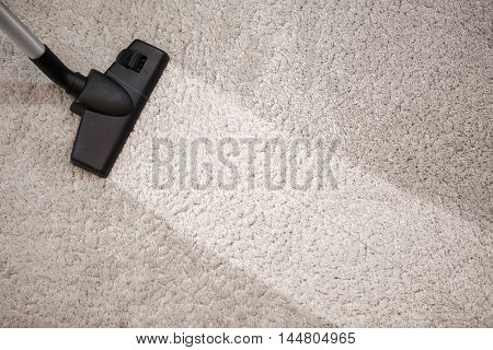 Head of vacuum cleaner in dusty carpet and clean strip
