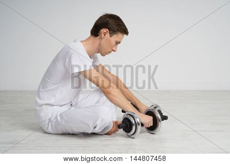 Man sitting on the floor with dumbbells. Resting time.