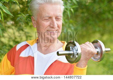 Elderly man exercising with dumbbell in  park