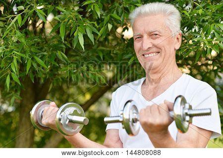 Elderly man exercising with dumbbells in  park
