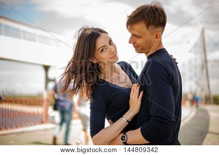 Side view of a couple standing and hugging on the street