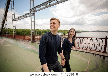 Young smiling couple walking on the bridge