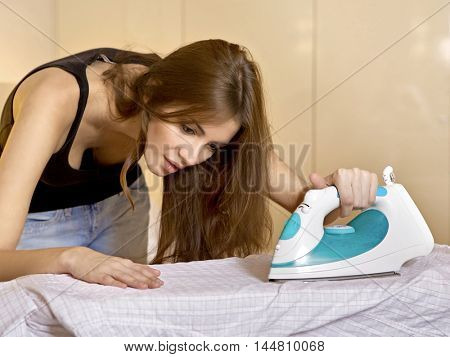Portrait of a beauty young adult attractive brunette woman ironing shirt on ironing board