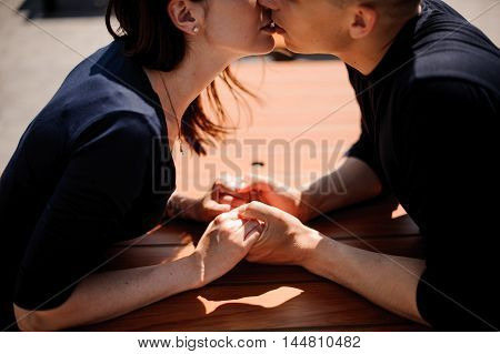 Couple kissing at the restaurant table outdoor