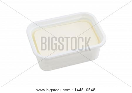 Rectangular container of feta cheese in a brined on a light background