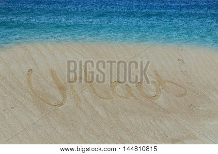 Golden sand with a drawn in the sand heart. Turquoise water and golden sand with a subscribed in the sand word in German holiday.