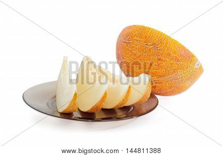 Several slices of a ripe yellow melon on a dark glass dish and half melon on a light background