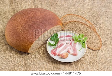Uncooked slices of streaky pork belly bacon sprigs parsley and coriander and garlic on saucer partly sliced brown wheat and rye hearth bread on a sackcloth