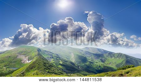 Mountain ranges with thicket of a mountain pine rocky outcrops alpine meadows and mountain lake on the background of sky with clouds