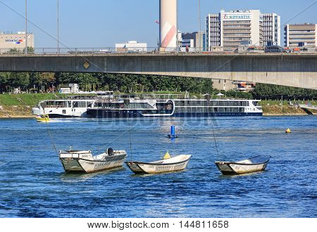 Basel, Switzerland - 27 August, 2016: boats on the Rhine river, the Dreirosenbruecke bridge and modern buildings in the background. Basel is a city in northwestern Switzerland on the Rhine river, situated where the Swiss German and French borders meet.
