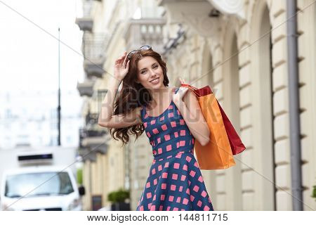 Young beautiful woman with shopping bags in the city- Let's go shopping concept