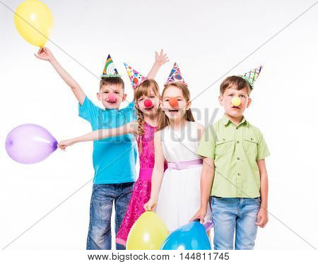 funny children with clown noses and birthday hats standing one by one
