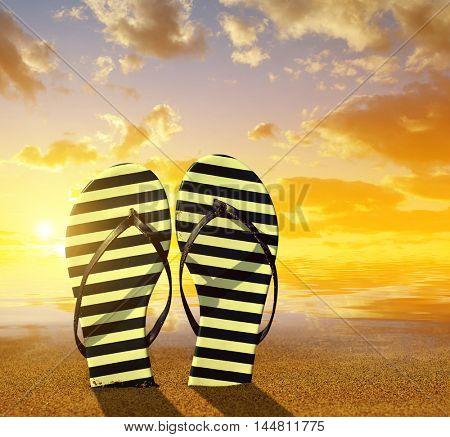 Flipflops on a sandy ocean beach at sunset. Summer vacation concept.