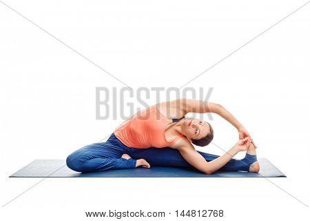 Beautiful sporty fit woman doing yoga asana parivrtta janu sirsasana - revolved head-to-knee pose isolated on white background