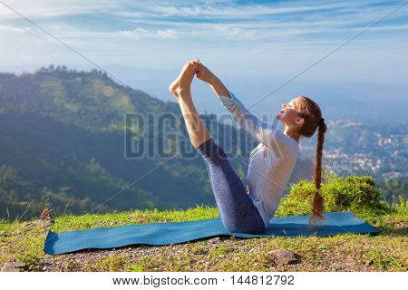 Yoga exercise outdoors -  woman doing Ashtanga Vinyasa Yoga balance asana Ubhaya padangusthasana Big Double Toe Yoga Pose in Himalayas in India in the morning