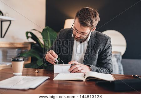 Young entrepreneur sitting at a table at home looking focused while stamping a seal on a package for delivery to a customer