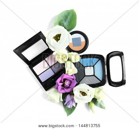 Eye shadows and flowers on white background